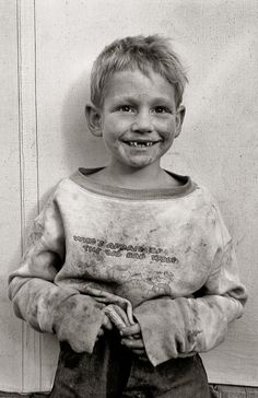 Migrant cotton picker's child who lives in a tent in the government camp instead of along the highway or in a ditch bank. Shafter Camp, California. November 1938. Dorothea Lange.