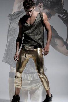 Male runway model wearing form fitting golden pants