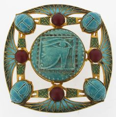 A Piel Freres Egyptian Revival enamelled metal belt buckle, rounded square section, set with a faience scarab beetle to each corner, central eye panel, with enamelled lotus fan stamped marks 7.0cm. wide.