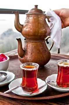 Copper Turkish tea pot with freshly brewed hot Turkish tea. Served in tulip glasses which are designed to keep the tea hot for a long time.