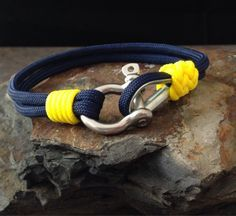 Michigan Wolverines Nautical Bracelet Paracord Bracelet With Stainless Steel Shackle & Thimble Clasp With Whipped End And Gaucho Knot.  ~~~~~~~~~~~~~~~~~~~~~~~~~~~~  All KnotOnlyParacord bracelets are handcrafted with high quality, made in the USA 550 (7 inner strands) Paracord and Type 1 Accessory Cord (vest cord.)   ~~~~~~~~~~~~~~~~~~~~~~~~~~~~  This Michigan Wolverines Nautical Bracelet is made with a stainless steel shackle and thimble for the clasp. A Gaucho Knot has been added using…