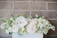 Half of the tables will have flowers in clear-glass rectangular vases with the stems showing....