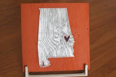 Show your love for your team and your town with this piece that shows all roads lead to Auburn!    The piece is hand painted, nailed, and strung on a 1ft by 1ft wooden board. The background is Auburn orange, the nails, string, and wood within Alabama's outline are silver, and a blue heart marks the town of Auburn. The wood grain even has a tiger stripe feel to it! It would make a great Christmas gift, decoration for a tailgate tent, or tribute to the team in the home of a Tiger fan.