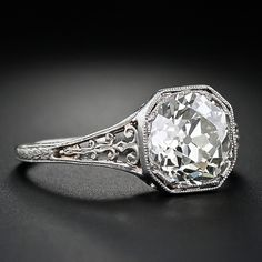 This absolutely show-stopping original Art Deco diamond ring features a dazzling 2.45 carat on Old Mine-cute diamond that is set high in its platinum octagonal mounting. The detailed mounting highlights open cut work shoulders and gallery with petite orange blossom motif
