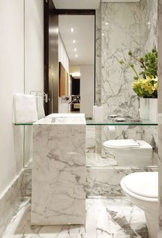 Chic powder room features floor to ceiling mirror framing floating glass shelf accented with marble waterfall atop marble tiled floor.