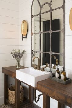 Beautiful rustic industrial bathroom design.  That mirror is incredible looking on the plank wood wall!