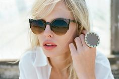 Perfect accessories for a white shirt in the summertime: shades and a big cocktail ring.