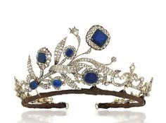 ANTIQUE SAPPHIRE & DIAMOND TIARA / NECKLACE. Composed of a central floral and foliate spray, each flowerhead with cushion shaped foil backed sapphire centre to an old-cut diamond openwork surround, raised on similarly-set diamond stems & scrolling leaves, to a series of graduated diamond fleur-de-lys motif panels, partially closed-set, mounted in silver & gold, the central spray with early 19th century elements detaching to form a brooch, the fleur-de-lys panels forming a necklace, circa…