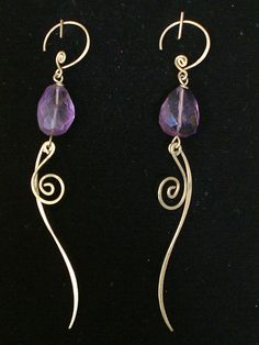 These earrings were made of cut amethyst hand wired with brass with dangling fire-shape hammered brass.