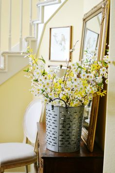 Vintage olive bucket with spring flowers. An easy way to add seasonal touches to your entry.
