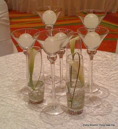 Mini calla lilies in bowed vases mixed with ball candles in small martini glasses