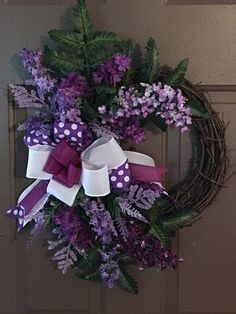 """This lilac spring wreath would look beautiful on your door. The grapevine measures 15"""" with the floral it measures 24""""."""