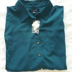 """💞SALE💞 F21 Hunter Green Long Sleeve Button up Brand New F21 Hunter Green Long Sleeve Button up. It is longer in back than front 25"""" from top of shoulder to bottom in front 29"""" from top of shoulder to bottom in back 24"""" from armpit to armpit 100% Polyester Forever 21 Tops Button Down Shirts"""