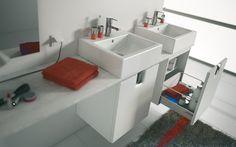 Dvě umyvadla postavená na desce doplněná úložnou skříňkou shodného designu. Kolekce Twins, Geberit