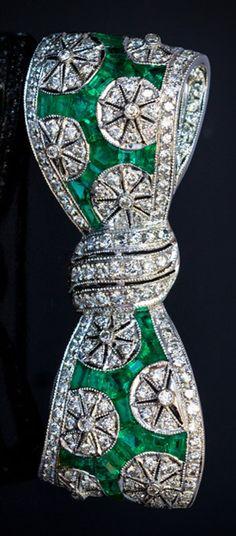 An Art Deco platinum, diamond and emerald bow brooch, circa 1930. Densely set with diamonds and calibré cut vivid green emeralds.