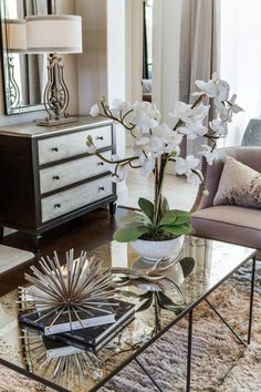 A beautiful white orchid breathes natural life into this chic living room. The houseplant pairs with other stylish accessories to create an eye-catching display atop the mercury glass coffee table.