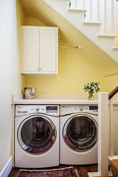 Basement features washer and dryer tucked in nook under staircase below upper cabinet and built-in ...
