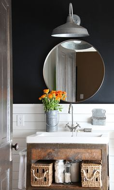 Bold color is easy to try in a small space. Here, upper walls are painted black while lower walls are covered with wood planks painted white. - Traditional Home ®