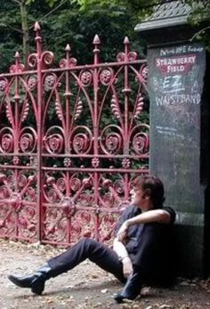 John Lennon sitting at the entrance of Strawberry Fields