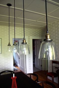 "Sneak Peek: A Massachusetts Farmhouse Where Color and Pattern Meet. ""We couldn't wait to rip down the old track lighting in our dining room.  It was replaced with four cloche pendant lights from Restoration Hardware, which were a gracious house-warming gift from dear friends.  The bulbs are Edison-style filaments that have such a lovely, warm glow."" #sneakpeek"