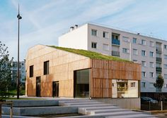 Grass blankets the roof of this low-energy community centre by Guillaume Ramillien Architecture