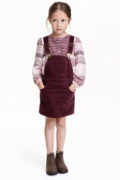 Manšestrová sukně s laclem: Manšestrová sukně s laclem a nastavitelnými ramínky. Má náprsní kapsu, přední a zadní kapsy a druky po stranách. V horní části podšívka.