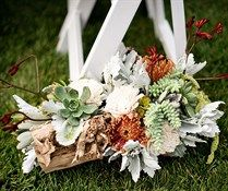 Este corredor é forrado de casamento com arranjos florais rústicas de suculentas, Dusty Miller, pincushions e amaranto.