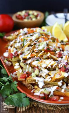 Chicken Shawarma Fries with Mediterranean Salsa and Garlic Sauce are a party on a platter! Full of delicious, fresh and bold flavors. | iowagirleats.com