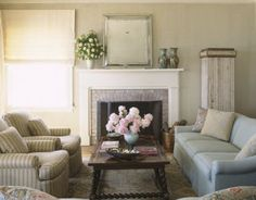 """The living room's """"Portuguese"""" coffee table is from JF Chen. The blue-green antique Oushak rug is from J. Iloulian. Over the mantel, the Duke mirror is by Jasper. The papier-mâché vases are 19th-century French. A pair of custom chairs is upholstered in Rose Tariow's Avalon striped linen in champagne, dusk, and sage. The custom sofa is covered in Pierre Frey's Croise Collobrières in celadon."""