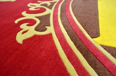 A fully Bespoke hand tufted wool rug in red and yellow. Created using the customers own design. [close up] #CustomRugRoom