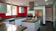 Diseño de cocina en pintira de poliuretano, con sistema de gola para la apertura de las puertas, mesón en quarztone gris absoluto.