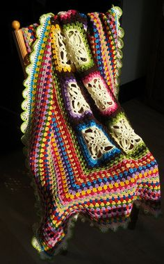 multi-coloured blankie. love the way the fancy squares are inside, bordered with granny square edging