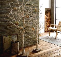 Lit Birch Tree. Branchy, lighted birch trees make an elegant addition to décor during the holidays and beyond. Bendable paper-wrapped branches have mini lights embedded in their tips. Each tree is mounted on reclaimed wood bases.