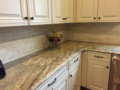My new kitchen! Typhoon Bordeaux granite with travertine tile backsplash and -white- cream glaze cabinets.