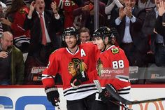 Duncan Keith #2 and Patrick Kane #88 of the Chicago Blackhawks celebrate after Kane scored against the Nashville Predators in the third period of the NHL game at the United Center on December 8, 2015 in Chicago, Illinois. The Chicago Blackhawks defeated the Nashville Predators 4 to 1.