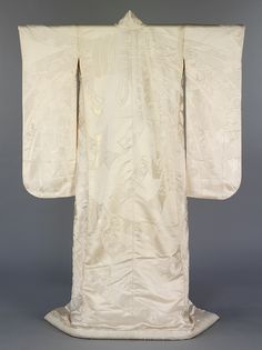 Kimono, Japan, 1980-2000, Woven silk, The traditional Japanese wedding ceremony takes place in a Shinto shrine and is attended by only close family members. The bride wears a white under-kimono and heavy white outer-kimono known as a shiromuku, shiro meaning white and muku meaning pure. This outer-kimono has a design of a large noshi, an auspicious ornament traditionally tied to goodwill gifts, the ribbons of which cascade down the front and back of the garment.