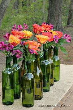 Wine and beer bottles with casual flowers for rehearsal dinner center pieces