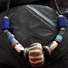 Tuareg Amulet with beads made of sandglass, wood with silver inlay, small silver beads and African flamed painted beads. (Necklace with onyx small beads)     Total Length: 58 cm     Please convo for more information!     Back to the webshop 'Vintage Tuareg Jewelry': http://www.etsy.com/shop/TuaregJewelry  https://www.facebook.com/TuaregJewelry  www.sahara-art-venture.com