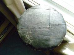 Coussin-pouf fait du vieux manteau de cuir.