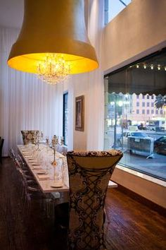 """Clear """"Ghost"""" chairs go toe-to-toe with baroque banquets and mod chandeliers in the dining room of the Saint Hotel on Canal Street in Nola."""