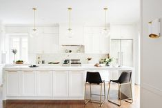 Large white and marble themed kitchen features a long white center island with a thick marble edge countertop detail joined with CB2 Roadhouse Black Leather Counter Stools under three glass and brass globe sconces.