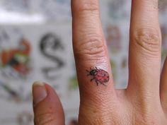 Lady bug tattoo on the forefinger