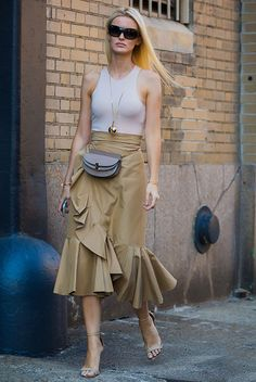 Sleek Ways To Style The Modern Fanny Pack: Kate Davidson wearing a white tank top, a beige ruffle midi skirt, nude heeled sandals, black sunglasses and a grey belt bag. Fanny pack, fanny pack outfit, belt bag, belt bag outfit, fashion trends 2018, fashion, fashion 2018, street style, party outfit, summer outfit, chic street style.
