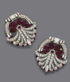 PAIR OF DIAMOND AND RUBY CLIPS CIRCA 1930, The modified circular clips of stylized floral design, set with carved ruby leaves, round cabochon rubies and buff-top calibré-cut rubies, further decorated with 218 round, baguette and marquise-shaped diamonds weighing a total of approximately 8.75 carats, mounted in platinum.