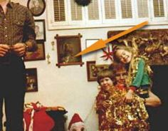 This is photo apparently taken in the 70's that shows the face of a small child inside the picture of Jesus behind the family. There were no other children there at the time picture was taken.