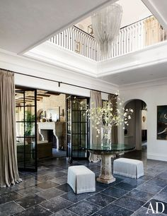 Gisele Bündchen and Tom Brady's House in Los Angeles [Architectural Digest]  ENTRY: A Hudson Furniture light fixture presides over the double-height entry.