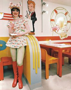 1970s Glam rock burger place waitress burger print minidress with green tights and bright red knee high go-go boots