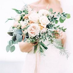 a beautiful blush and cream rose wedding bouquet with textural greenery for a neutral colored wedding