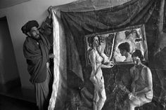 Abbas AFGHANISTAN. City of Kabul. 2001. A guardian of the National Gallery exhibits a painting of two naked women which was taken off its frame by the Taliban to be locked off in a gallery's room.