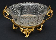 BACCARAT - Fabuloso centro de mesa em cristal francês prensado decorado com espirais em relevo, borda recortada, com suporte em bronze ormolu ricamente cinzelado no estilo art nouveau. Peça marcada. Med.: 17x33 cm.